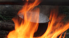 water boils in a camping kettle on a fire, strong hot fire - stock footage