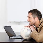 Businessman on soccer ball Stock Photos