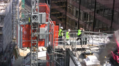 Construction workers on top of tall building - stock footage