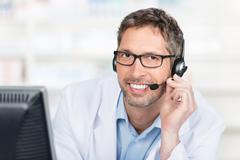 smiling pharmacist wearing headset at counter - stock photo
