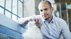 Man relaxing at home and giving lots of affection to his beautiful pet cat Stock Footage