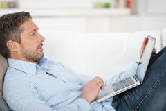 Mature man holding laptop on couch Stock Photos