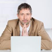 Serious businessman with laptop in office Stock Photos