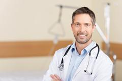 Smiling doctor with arms crossed standing in hospital Stock Photos