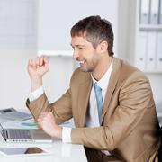 Successful businessman with laptop at desk Stock Photos