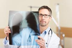 serious mature doctor holding x-ray report in hospital - stock photo