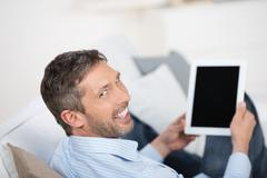 rear view of mature man holding tablet pc on sofa - stock photo