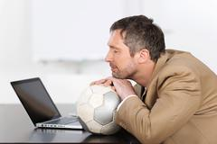 businessman with eyes closed resting chin on soccer ball - stock photo