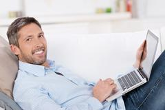 mature man holding laptop on sofa - stock photo