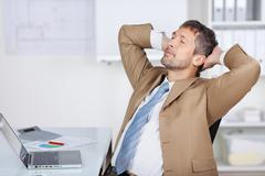 businessman with hands behind head sleeping at desk - stock photo