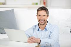 mature man with laptop in house - stock photo