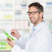 pharmacist holding prescription paper and product in pharmacy - stock photo