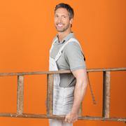 Stock Photo of painter carrying wooden ladder against orange painted wall