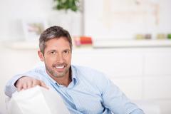 mature man sitting on sofa - stock photo