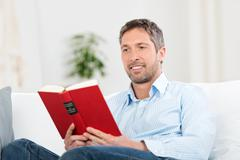 man reading book in house - stock photo