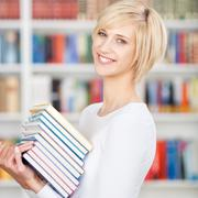 young woman carrying stacked books in library - stock photo