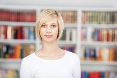 blond woman standing in library - stock photo