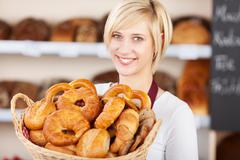 Saleswoman in bakery showing various bread loafs Stock Photos