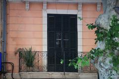 Wooden door and wrought iron balcony Stock Photos