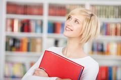 smiling student holding binder in library - stock photo