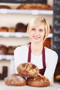 Smiling salesgirl working in bakery Stock Photos
