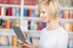 young woman using tablet-pc in library - stock photo