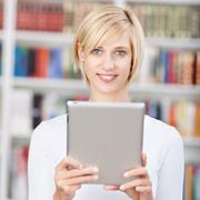 female student holding digital tablet in library - stock photo