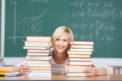 female student with stacked books at desk - stock photo