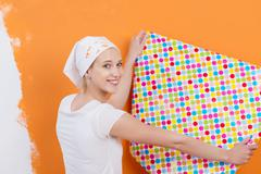 Woman holding wallpaper against orange colored wall Stock Photos