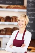 Waitress with arms crossed standing in bakery Stock Photos