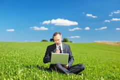 Businessman sitting outdoors thinking Stock Photos