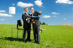 two businessmen in field - stock photo