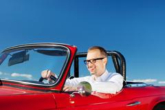 smiling man driving a red cabriolet - stock photo