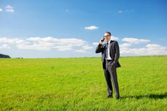 Businessman phoning from a green field Stock Photos