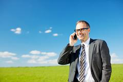 man using his mobile in a spring pasture - stock photo
