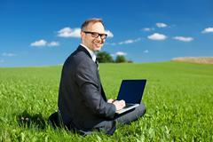 businessman working outdoors under a blue sky - stock photo