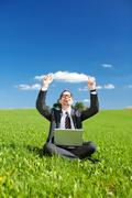 Successful man working outdoors in a green field Stock Photos