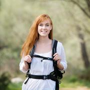 young woman out hiking with a rucksack - stock photo