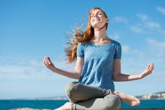 Beautiful woman meditating at the seaside Stock Photos