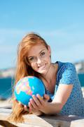 Smiling woman with a globe at the seaside Stock Photos