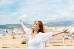 woman on a rooftop embracing the sunshine - stock photo