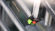 Stock Video Footage of Construction worker suspended on side of a building with ropes