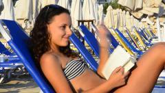 Happy beautiful teen girl sunbathing & reading book at the beach hd. lie on b Stock Footage