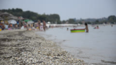 Sandy beach, focus on sand with blurred people Stock Footage