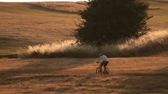 Mountain Cyclist Cycling Through Field at Sunset HD Stock Footage