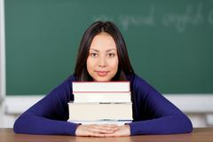 happy young woman leaning head on books - stock photo