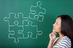 young woman completing puzzle - stock photo