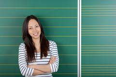 smiling female student with crossed arms - stock photo