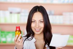 Stock Photo of young pharmacist holding medicine and prescription