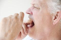 older man flossing teeth profile view - stock photo